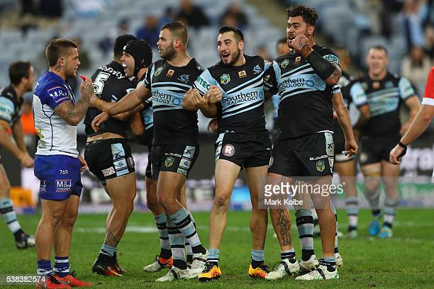 Craig Garvey of the Bulldogs looks dejected as Valentine Holmes Michael Ennis Wade Graham Jack Bird and Andrew Fifita of the Sharks celebrate victory...