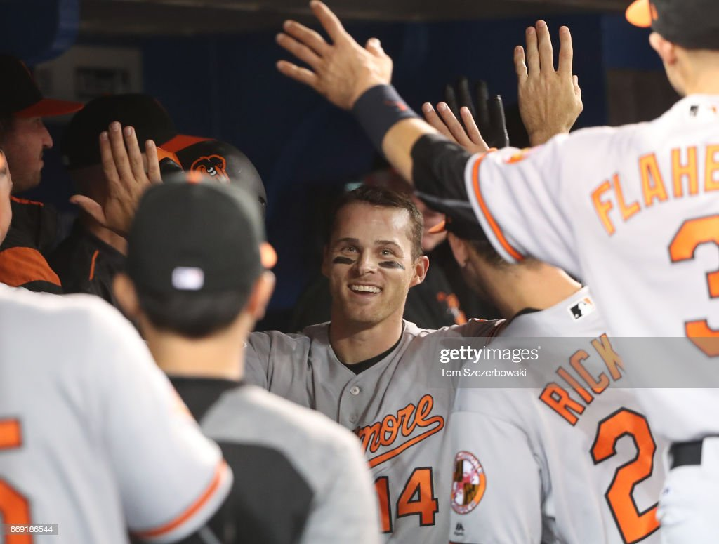 Craig Gentry #14 of the Baltimore Orioles is congratulated by teammates in the dugout after hitting a home run in the eighth inning during MLB game action against the Toronto Blue Jays at Rogers Centre on April 16, 2017 in Toronto, Canada.