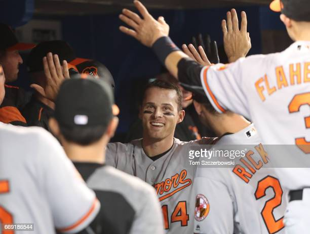 Craig Gentry of the Baltimore Orioles is congratulated by teammates in the dugout after hitting a home run in the eighth inning during MLB game...