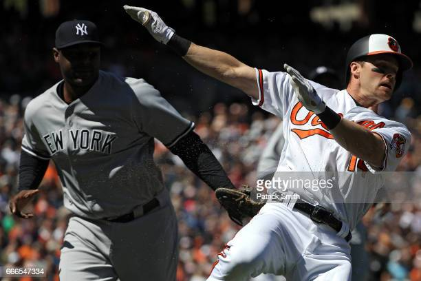 Craig Gentry of the Baltimore Orioles is tagged out by first baseman Chris Carter of the New York Yankees during the first inning at Oriole Park at...