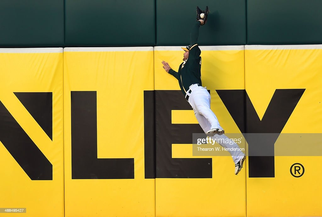 Craig Gentry #3 of the Oakland Athletics leaps at the wall to take a hit away from Corey Hart #27 of the Seattle Mariners (not pictured) in the top of the first inning at O.co Coliseum on May 6, 2014 in Oakland, California.