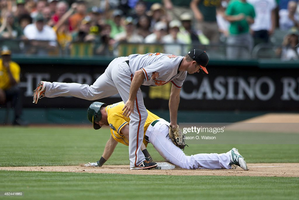 Craig Gentry #3 of the Oakland Athletics slides into third base ahead of a tag from J.J. Hardy #2 of the Baltimore Orioles during the fifth inning at O.co Coliseum on July 20, 2014 in Oakland, California. The Oakland Athletics defeated the Baltimore Orioles 10-2.