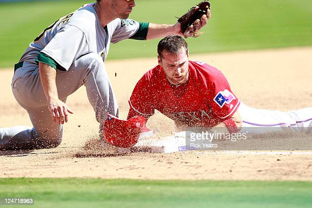 Craig Gentry of the Texas Rangers beats the tag at third base against Scott Sizemore of the Oakland Athletics at Rangers Ballpark in Arlington on...