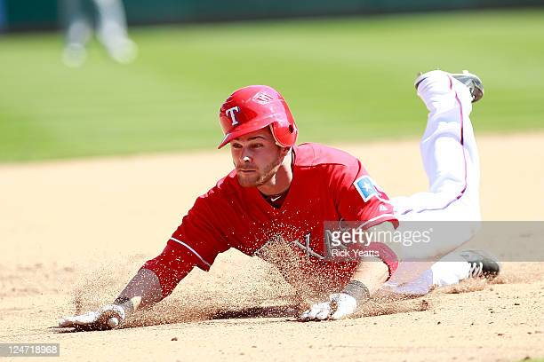 Craig Gentry of the Texas Rangers dives into third base against the Oakland Athletics at Rangers Ballpark in Arlington on September 11 2011 in...