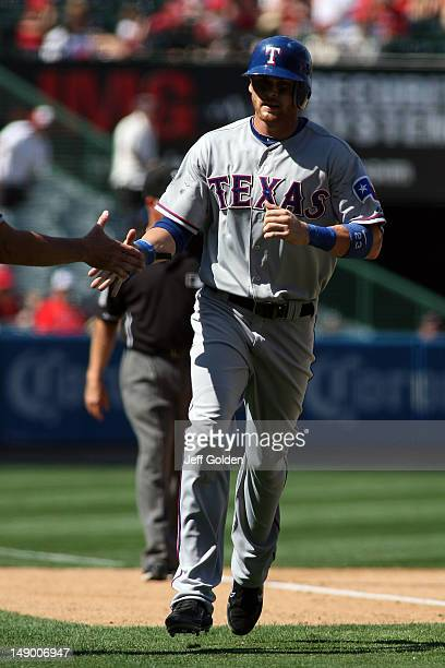 Craig Gentry of the Texas Rangers rounds third base against the Los Angeles Angels of Anaheim on his way to scoring on a tworun home run by teammate...