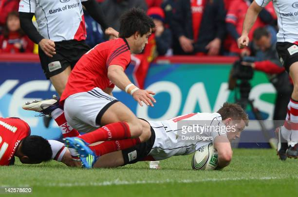 Craig Gilroy of Ulster scrambles over the line to score the first try during the Heineken Cup quarter final match between Munster and Ulster at...