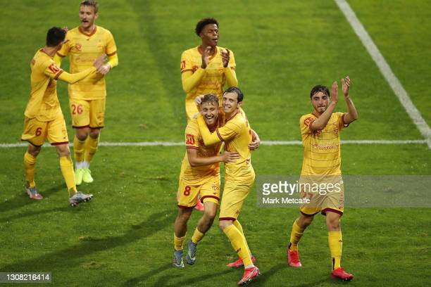 Craig Goodwin of Adelaide United celebrates scoring a goal with team mates during the A-League match between the Newcastle Jets and Adelaide United...