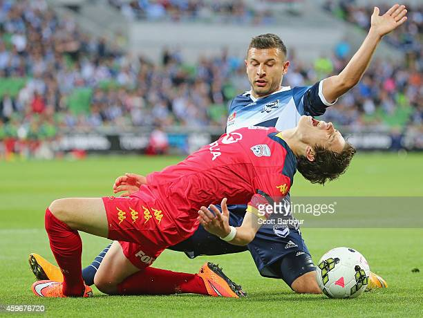 Craig Goodwin of United is tackled and fouled by Kosta Barbarouses of the Victory during the round eight A-League match between Melbourne Victory and...