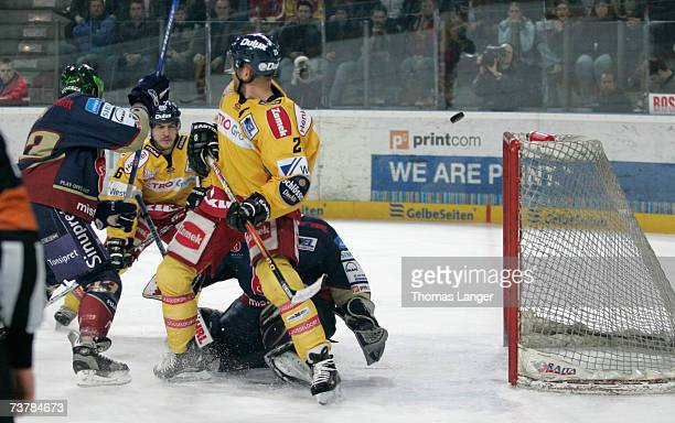 Craig Johnson of Dusseldorf lifts the puck over goalie Jean-Francois Labbe and scores the first goal during the DEL Play Off semi final match between...