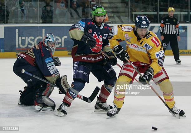 Craig Johnson of Dusseldorf , Michel Periard and Jean-Francois Labbe battle for the puck lduring the DEL Play Off semi final match between Sinupret...