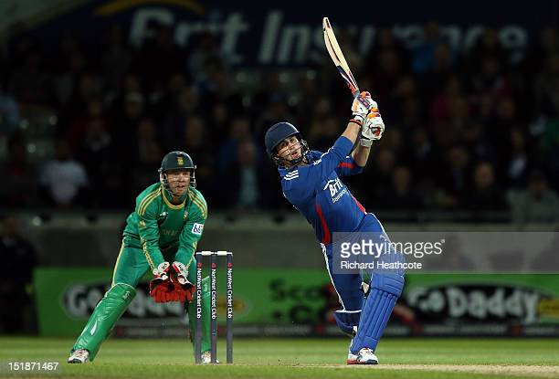 Craig Kieswetter of England smashes a six as AB de Villiers of South Africa looks on during the 3rd NatWest International T20 between England and...
