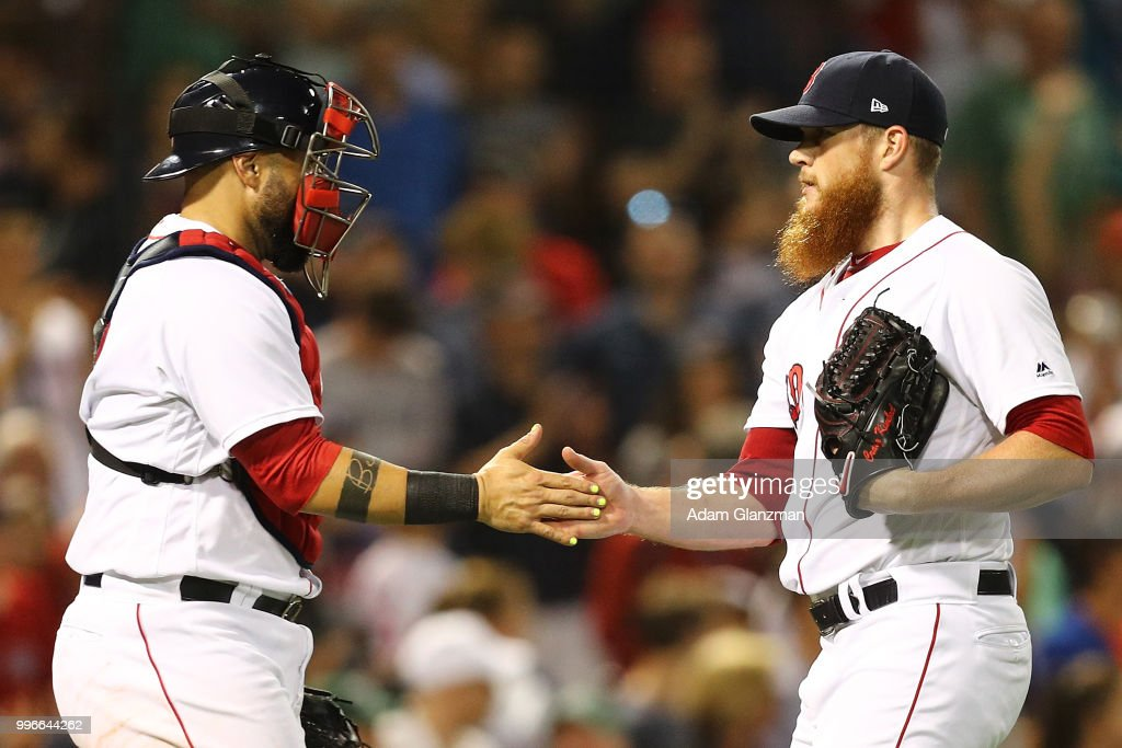 Craig Kimbrel #46 high fives Sandy Leon #3 of the Boston Red Sox after a victory over the Texas Rangers at Fenway Park on July 11, 2018 in Boston, Massachusetts.