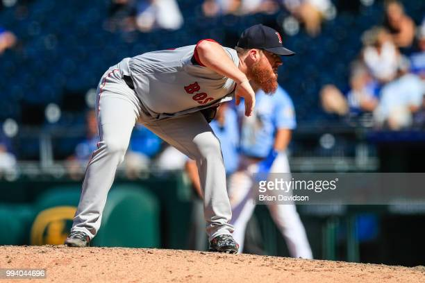 Craig Kimbrel of the Boston Red Sox checks the sign before the pitch during the ninth inning against the Kansas City Royals at Kauffman Stadium on...