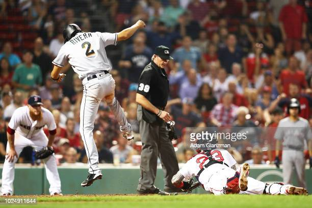 Craig Kimbrel of the Boston Red Sox looks on as Yadiel Rivera of the Miami Marlins slides safely into home plate under the tag of Blake Swihart of...