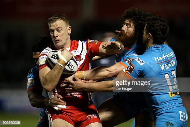 Craig Kopczak of Salford Red Devils crashes into Kyle Amor and Jon Wilkin of St Helens during the First Utility Super League match between Salford...