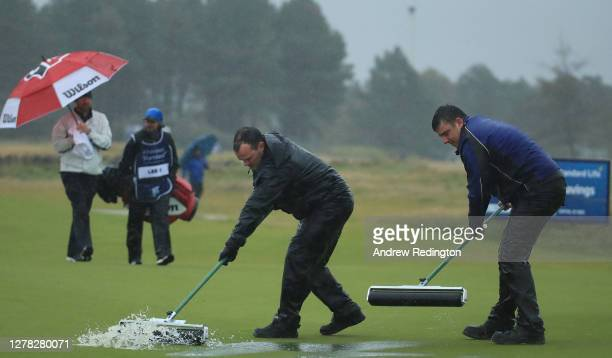 Craig Lee of Scotland looks on while greenkeepers clear water from the 18th green during third round of the Aberdeen Standard Investments Scottish...