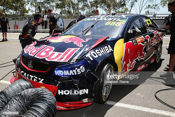 Craig Lowndes driver of the Red Bull Racing Australia Holden returns to the pits to receive repairs for damage to his car from a accident during...