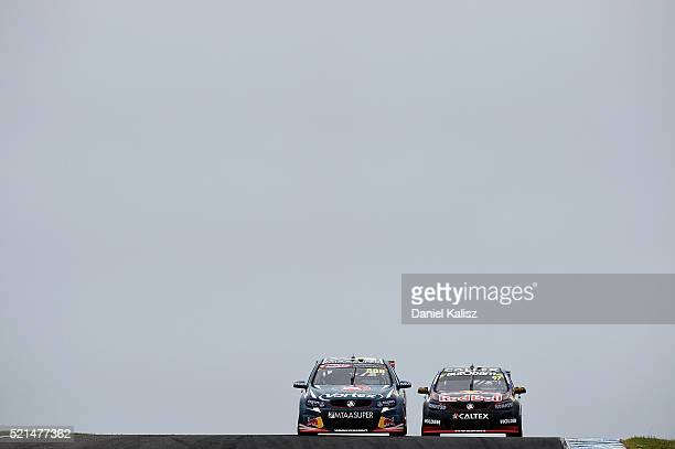 Craig Lowndes drives the TeamVortex Holden Commodore VF leads Shane Van Gisbergen drives the Red Bull Racing Australia Holden Commodore VF during the...