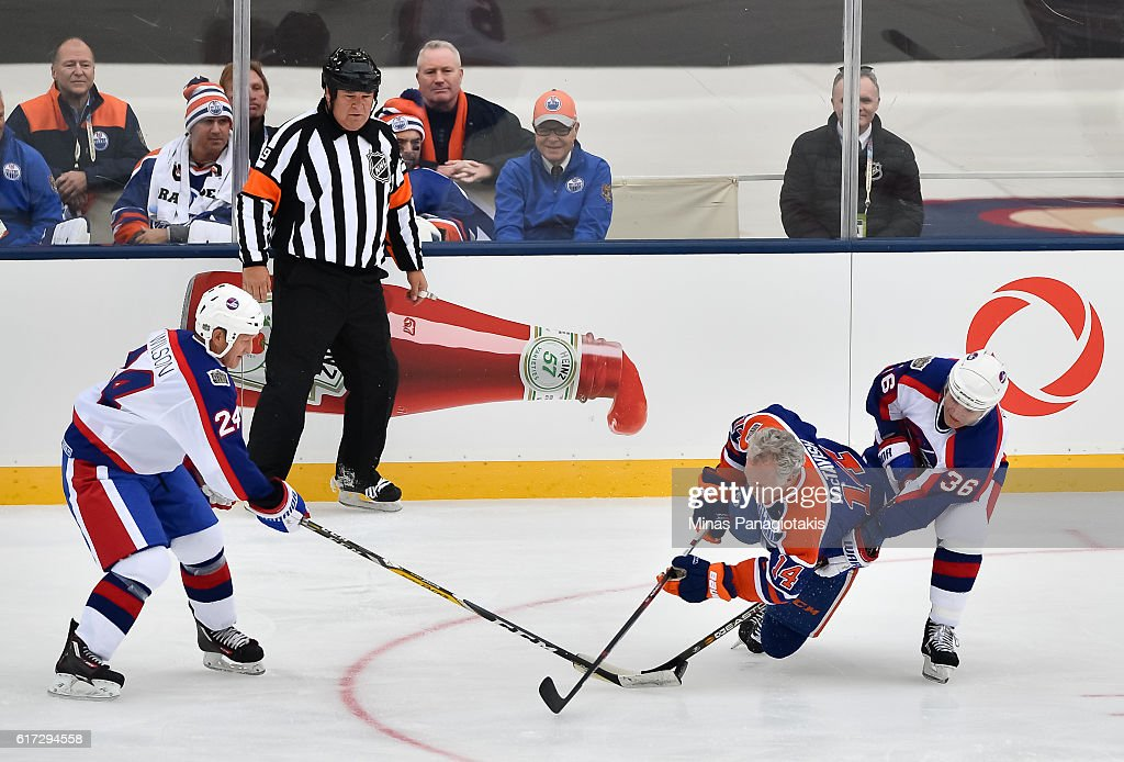 Craig MacTavish #14 of the Edmonton Oilers alumni collides with Mike Eagles #36 of the Winnipeg Jets alumni during the 2016 Tim Hortons NHL Heritage Classic alumni game at Investors Group Field on October 22, 2016 in Winnipeg, Canada.