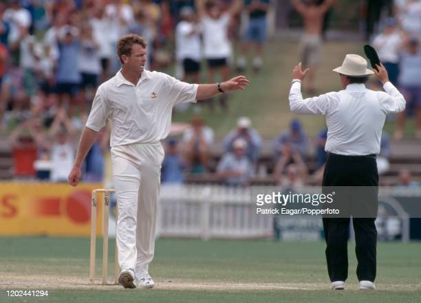 Craig McDermott of Australia reaches for his cap as umpire Peter Parker signals a six hit by England batsman Phillip DeFreitas during the 4th Test...