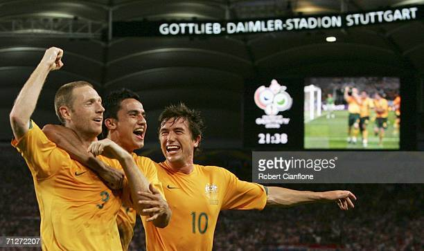 Craig Moore of Australia celebrates with teammates Tim Cahill and Harry Kewell after converting a penalty to level the scores at 11 during the FIFA...