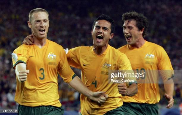 Craig Moore of Australia celebrates with teammates Tim Cahill and Harry Kewell after taking a penalty to level the scores at 11 during the FIFA World...