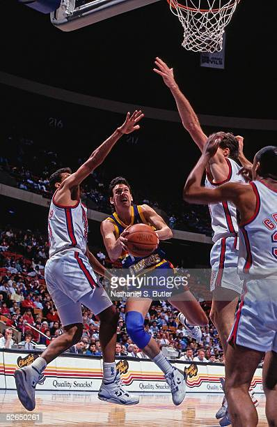 Craig Neal of the Denver Nuggets drives to the basket against the New Jersey Nets during the NBA game at the Brendan Byrne Arena circa 1991 in East...