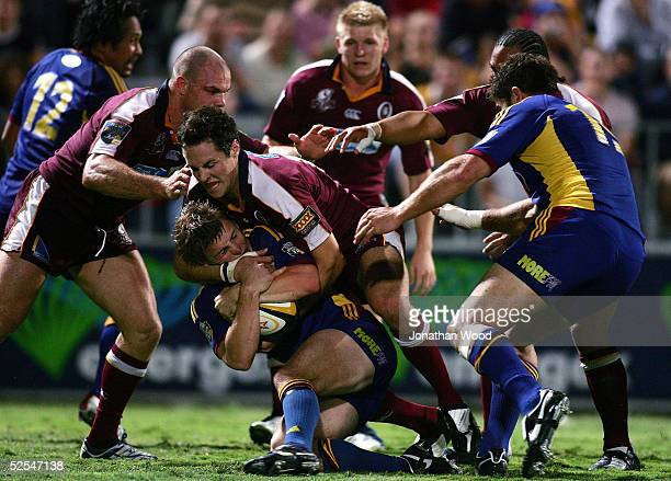 Craig Newbie of the Highlanders is tackled by Julian Huxley of the Reds during the Super 12 Match between the Queensland Reds and Highlanders at...