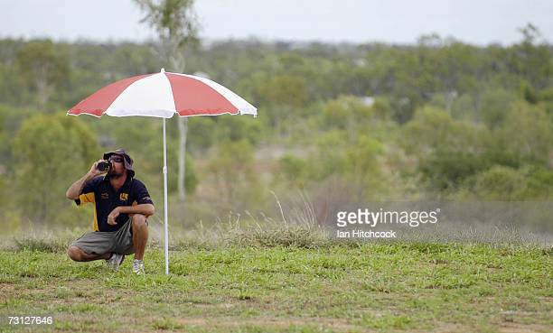 Craig Newell of the team 'Violators' drinks a beer under his unbrella whilst fielding during the Goldfield Ashes January 26 2007 in Charters Towers...