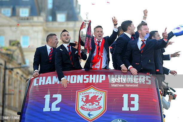 Craig Noone of Cardiff City FC holds the trophy aloft as he and teammates ride in an open top bus through the city centre during a victory parade in...