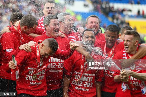 Craig Noone of Cardiff City sprays champagne on Craig Bellamy during championship victory celebrations after the npower Championship match between...
