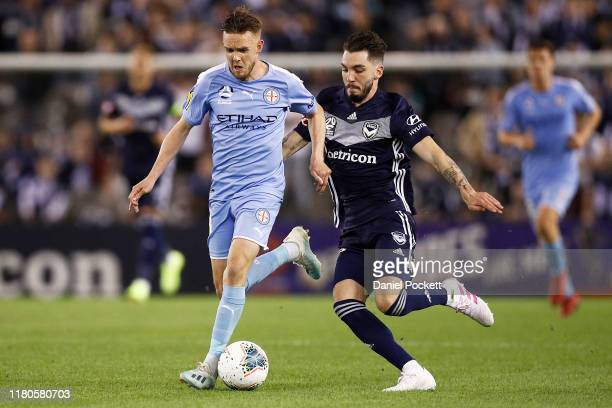 Craig Noone of Melbourne City and Storm Roux of the Victory contest the ball during the round one A-League match between the Melbourne Victory and...