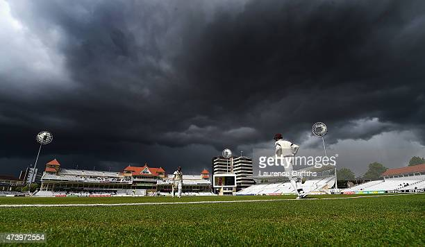 Craig Overton of Somerset walks out to bat as Alexander Barrow returns to the pavilion under stormy skies during the LV County Championship match...