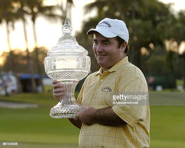Craig Parry of Australia hoists the winner's trophy after the final round of the PGA Tour Ford Championship at Doral in Miami, Florida March 7, 2004....
