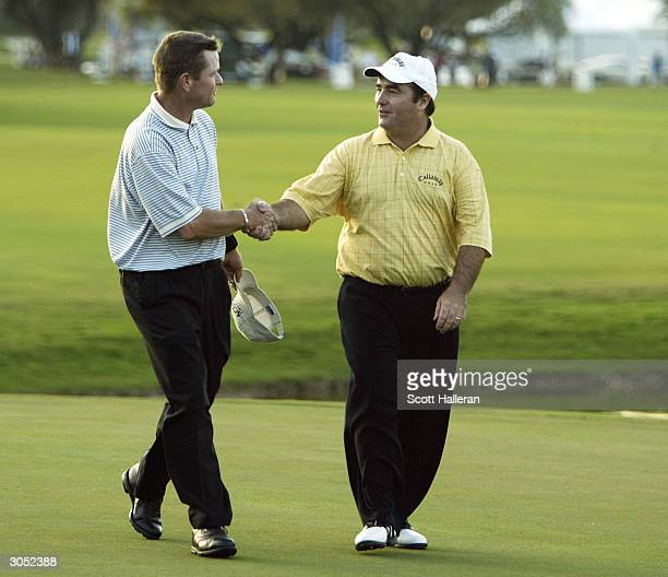 Craig Parry of Australia shakes hands with Scott Verplank after holing a shot for eagle to defeat Scott Verplank on the first playoff hole at the...