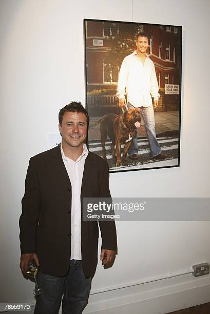Craig Phillips poses infront of his calendar photograph with his Bull Mastiff Raffiki at the Launch of the 2008 Pdsa Calendar 'Pawtraits of...
