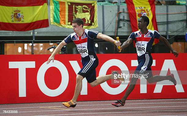 Craig Pickering of Great Britain receives the baton from Christian Malcolm of Great Britain during the Men's 4 x 100m Relay First Round on day seven...