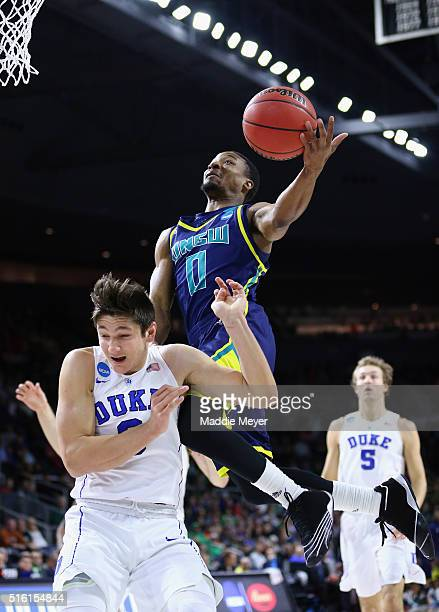 Craig Ponder of the North CarolinaWilmington Seahawks drives to the basket against Grayson Allen of the Duke Blue Devils in the first half of their...