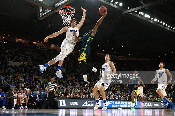 Craig Ponder of the North CarolinaWilmington Seahawks goes to the basket against Grayson Allen of the Duke Blue Devils during the first round of the...