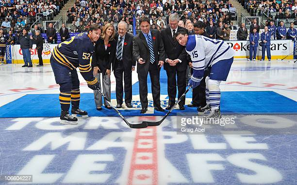 Craig Rivet of the Buffalo Sabres and Tomas Kaberle of the Toronto Maple Leafs take part in a cerimmonial face-off with Hockey Hall Of Fame inductees...