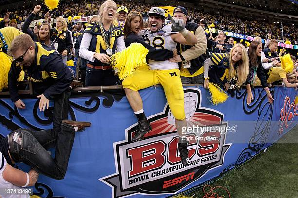 Craig Roh of the Michigan Wolverines celebrates with fans and students after Michigan won 2320 in overtime against the Virginia Tech Hokies during...