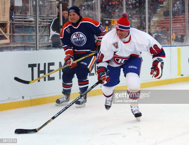 Craig Simpson of the Edmonton Oilers watches as JJ Daigneault of the Montreal Canadiens chases after the play during the Molson Canadien Heritage...