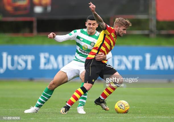Craig Slater of Partick Thistle vies with Tomas Rogic of Celtic during the Betfred Scottish League Cup round of sixteen match between Partick Thistle...