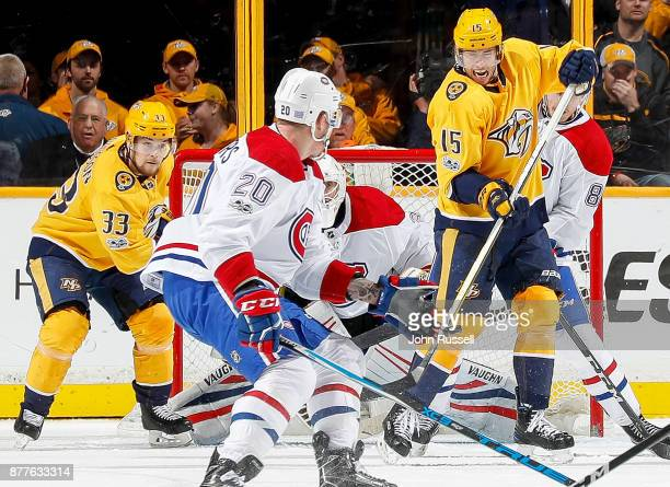 Craig Smith and Viktor Arvidsson of the Nashville Predators battle in front of goalie Antti Niemi of the Montreal Canadiens during an NHL game at...