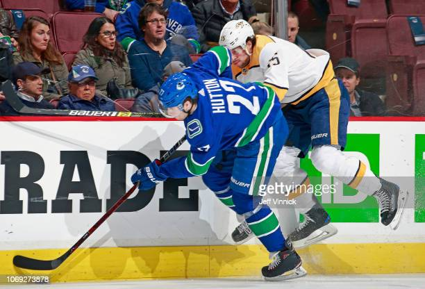 Craig Smith checks Ben Hutton during their NHL game at Rogers Arena December 6, 2018 in Vancouver, British Columbia, Canada.