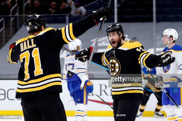 Craig Smith of the Boston Bruins celebrates with Taylor Hall after scoring a goal against the Buffalo Sabres during the first period at TD Garden on...