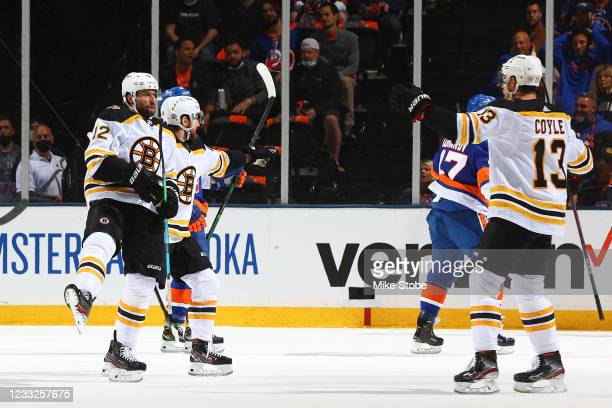 Craig Smith of the Boston Bruins is congratulated by his teammates after scoring a goal against the New York Islanders during the first period in...