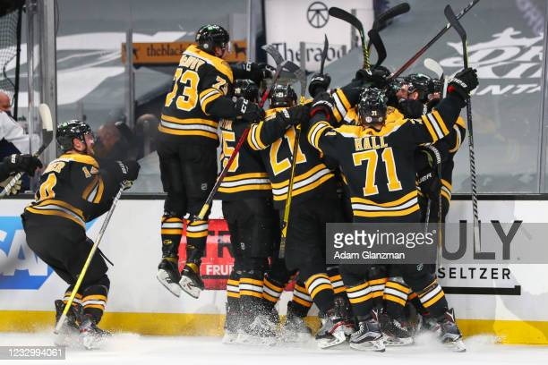 Craig Smith of the Boston Bruins reacts with teammates after scoring the game-winning goal in double overtime against the Washington Capitals in Game...