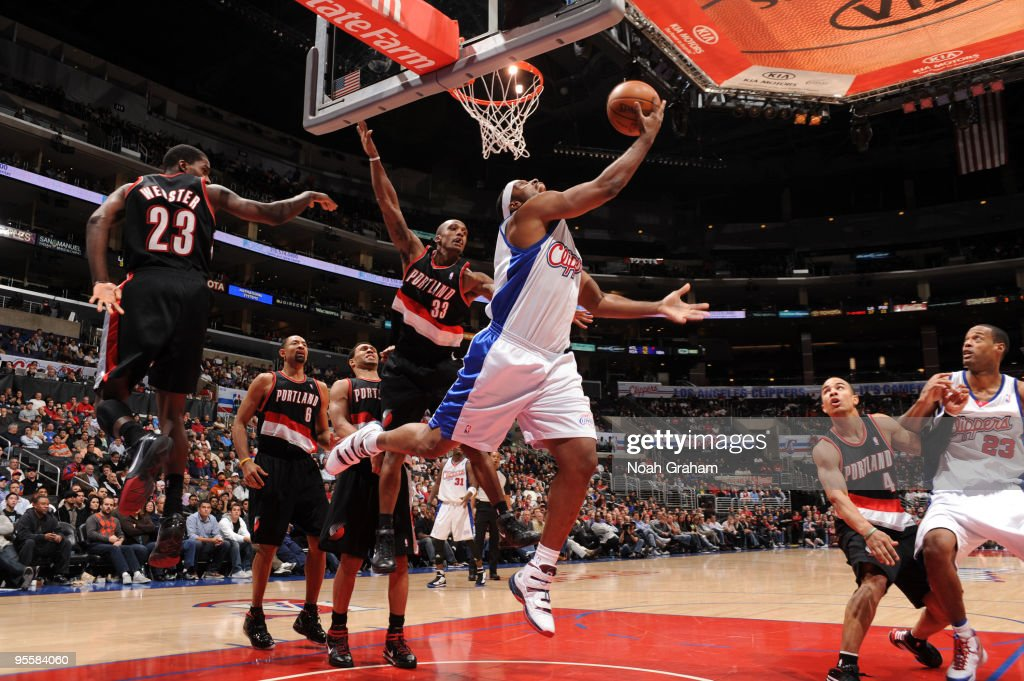 Craig Smith #5 of the Los Angeles Clippers goes up for a reverse layup against Martell Webster #23 and Dante Cunningham #33 of the Portland Trail Blazers at Staples Center on January 4, 2010 in Los Angeles, California.