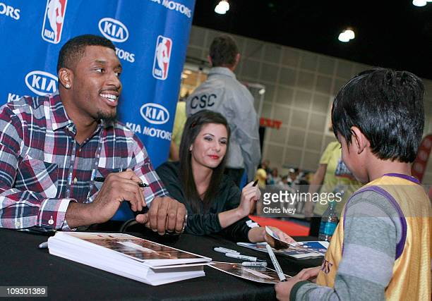 Craig Smith of the Los Angeles Clippers signs autographs for fans during an appearance at the Kia MVP Court at Jam Session presented by Adidas during...